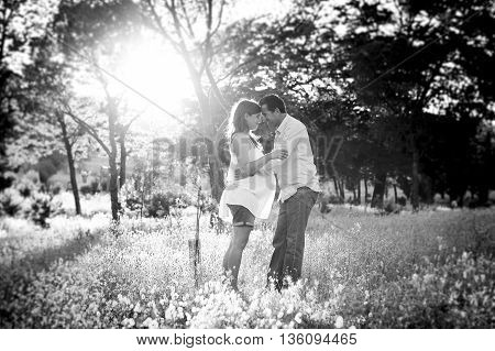 young happy beautiful couple in love walking together on grass and trees park landscape on sunset in summer with man touching pregnant belly of his woman in family concept in black and white