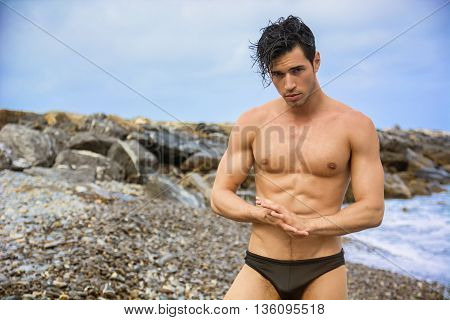 Attractive muscular young shirtless athletic man standing next to water by sea or ocean shore, wearing trunks or swimming suit, looking at camera in a cloudy summer day