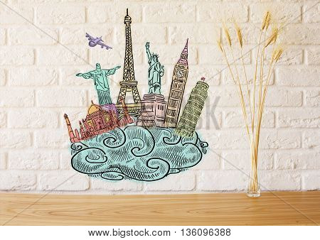 Front view of sights sketch on white brick wall above wooden desktop with decorative wheat spikes. Travel concept
