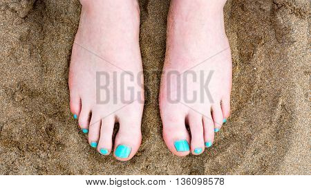 Toes against sand at the beach with painted nails
