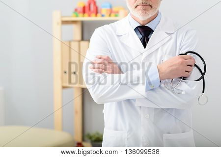 Your health is his priority. Close up of mature doctor holding stethoscope with his arms folded