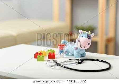 Plush patient. Close up of plush toy and pills with stethoscope device on top of white table