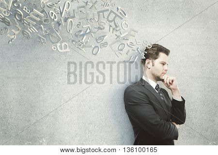 Thinking businessman with hand at chin standing against concrete wall