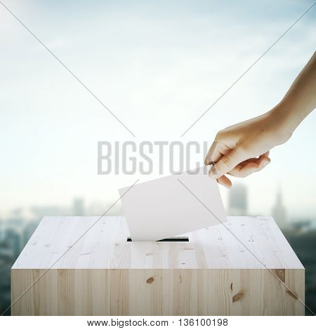 Hand with blank ballet casting vote into wooden ballot box on blurry city background. Voting concept. Mock up 3D Rendering