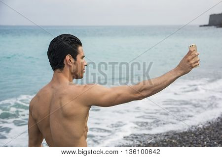 Side View of a Shirtless Young Man Taking Selfie Photos at the Beach While Standing Under the Sun.