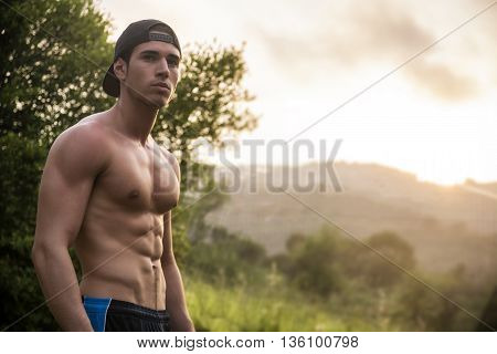 Attractive muscular shirtless young man in nature in front of green plants and trees, looking away, at sunset with gorgeous dusk light