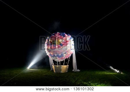 Fake ball standing on field, made of paper flowers