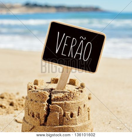 closeup of a sandcastle on the sand of a beach topped with a black signboard with the text verao, summer in Portuguese written in it