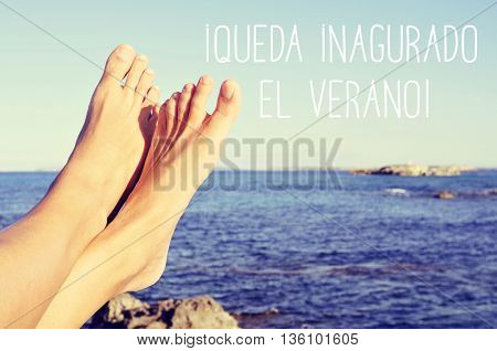 closeup of a barefoot young man in front of the ocean and the text queda inaugurado el verano, the summer is inaugurated, written in Spanish