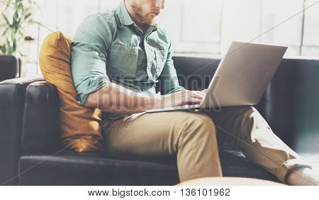 Bearded Hipster working Laptop modern Interior Design Loft Office.Man work Classic Sofa, Use contemporary Notebook, typing keyboard.Blurred Background.Creative Business Startup Idea.Horizontal, Film
