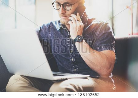 Muscular Bearded Hipster working Laptop modern Interior Design Loft Office.Man Sitting Vintage Sofa.Using contemporary Smartphone Hand.Blurred Background.Creative Business Startup Process Idea.Film