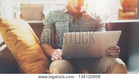 Bearded Businessman work Laptop modern Design Interior Loft Studio Place.Man relaxing Vintage Sofa.Use contemporary Notebook Send Message.Blurred background.Creative Process Startup Idea.Film effect
