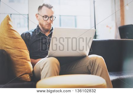 Bearded Trader working Laptop modern Design Interior Open Space Loft.Handsome Man work Vintage Sofa.Use contemporary Notebook, Browsing Internet.Blurred Background.Business Startup Process.Film effect