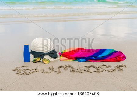 Sunglasses, sun cream and hat  on white  sand beach