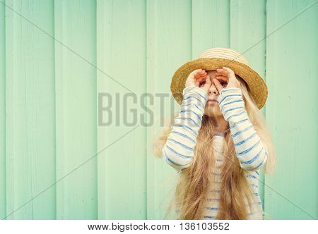 Cute little girl stands near a turquoise wall in boater hat and and looks invented binoculars. Space for text. Negative speace.