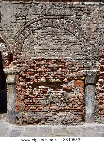 Brick wall with closed arch and columns buried in the old street level of Venice