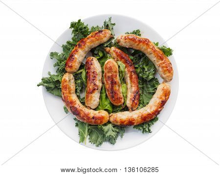 Links of the cooked homemade sausages on the plate with cale