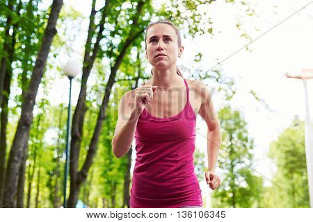 Young sporty woman looks concentrated and motivated while running in the park
