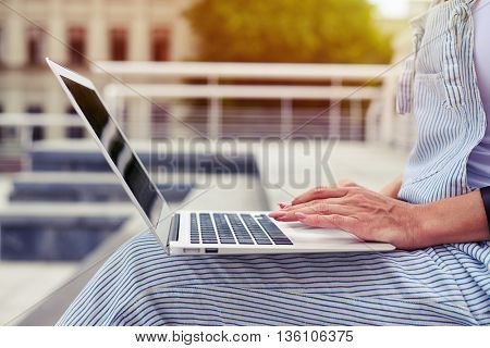 Close-up on female hands with nude manicure on touchpad of laptop she is holding on her knees outdoors on warm day