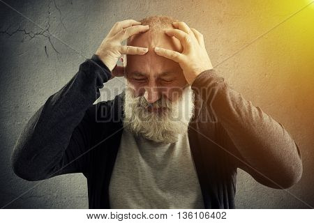 Stylish aged man with white beard in casual clothes is holding his head with fingers against grey concrete wall with yellow shining on one side