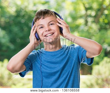 Teen boy smiling listening a music in headphones, posing outdoors. Looking at camera.