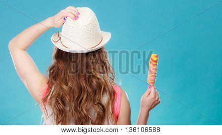 Young woman with long hair wearing white hat holding ice cream on blue background. Rear view.