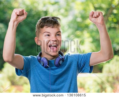Victory screaming teen boy 12-14 year old. Winner boy with headphones and sunglasses posing outdoors.