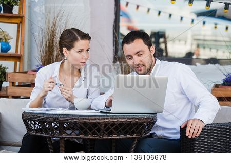 Businessman and businesswoman working outdoor at street cafe during the lunch.