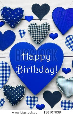 Blue Vertical Heart Texture With English Text Happy Birthday. White Wooden Background. Textile Hearts Which Are Dotted and Striped. Greeting Card With Congratulations