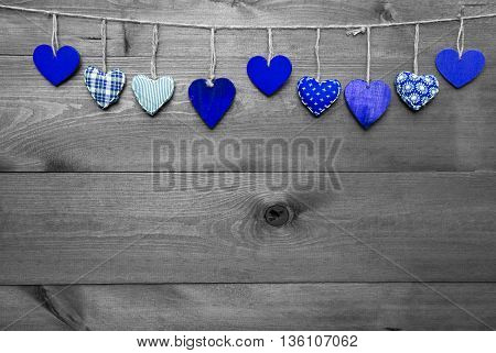 Wooden Background With Blue Hearts Hanging In A Row. Black And White Style With Colored Hot Spots. Copy Space For Advertisement Or Free Text. Greeting Card For Mothers Or Valentines Day
