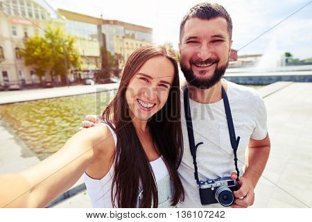 Young beautiful smiling couple is making a selfie on a wonderful sunny day against the fountain in recreational area of the city