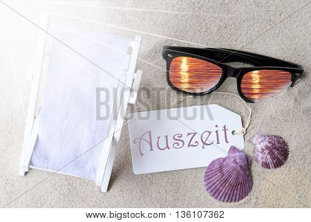 Sunny Summer Label With German Text Auszeit Means Relax. Flat Lay View. Summer Decoration With Deck Chair, Seashells And Sunglasses. Greeting Crad With Sand Background