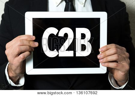 Business man holding a tablet with the text: C2B