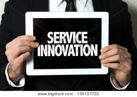 Business man holding a tablet with the text: Service Innovation