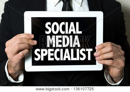 Business man holding a tablet with the text: Social Media Specialist