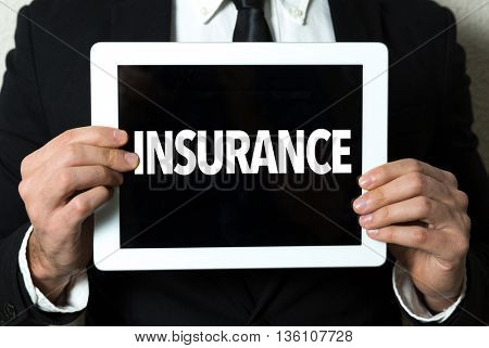 Business man holding a tablet with the text: Insurance
