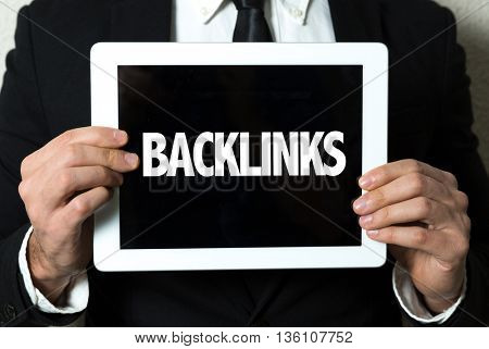Business man holding a tablet with the text: Backlinks