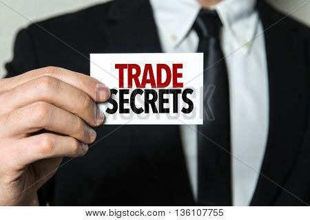 Business man holding a card with the text: Trade Secrets