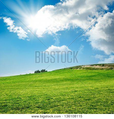 green field over sunny sky
