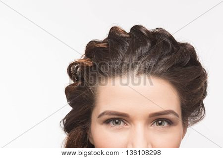 Closeup portrait of top view of woman's face represented with beautiful hairstyle - hair braids concept over white background.