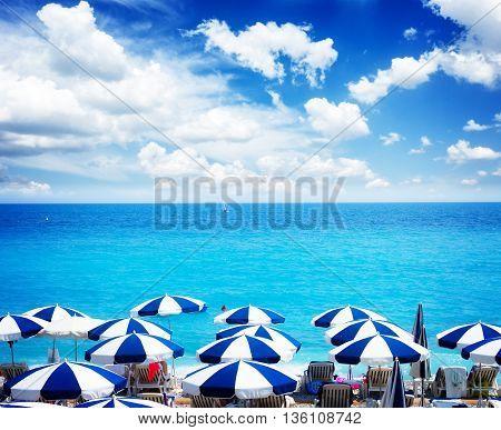 turquiose water of cote dAzur over beach umbrellas under summer sky, France, retro toned