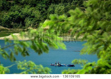 fishermen fishing on lake with small boats