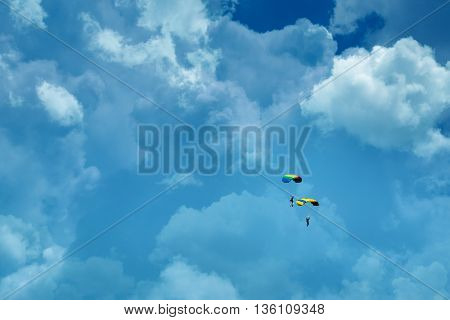 two people parachuting in cloudy sky