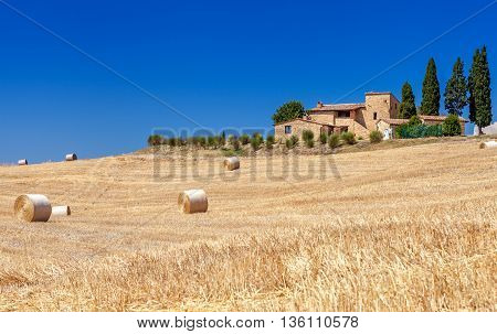 Montepulciano Italy - August 25 2013: Rural landscapes of Tuscany Italy. Lots of round bales and haystacks in the fields. Brick farmhouse standing on a hill among the pitch.