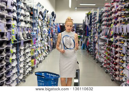 Beautiful caucasian woman shopping sports equipment in sportswear store.