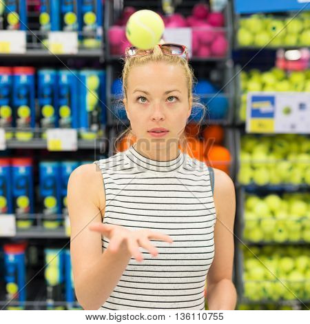 Beautiful caucasian woman shopping sports equipment in sportswear store. Lady throwing tennis ball in the air.