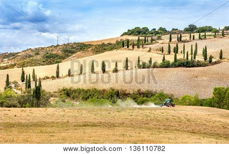 Montepulciano Italy - August 27 2013: Agriculture plowing tractor with a cultivator plow the field after the harvest. Winding road with cypresses in Tuscany.