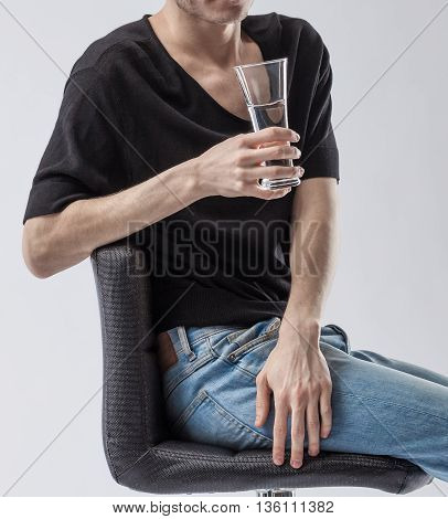 Man holding a glass of clean drinking water. Closeup