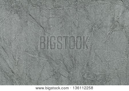 Light gray wavy background from a textile material. Fabric with natural texture closeup. Upholstery fabric pleated.