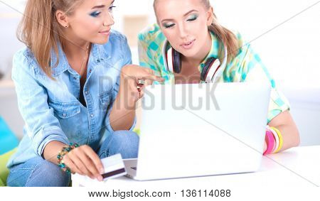 Two young women sitting with laptop  and credit cart at home